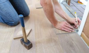 person measuring flooring for a home renovation
