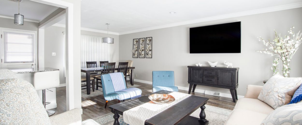 light living room with chairs, coffee table and a TV